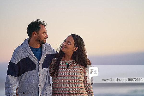 Glückliches Liebespaar umarmt sich am Strand
