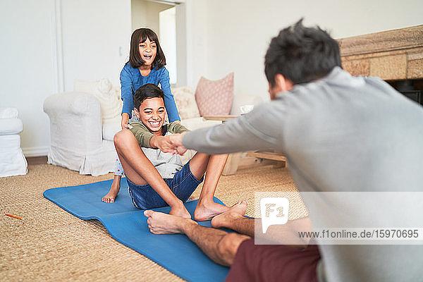 Glückliche Familie beim Sport im Wohnzimmer