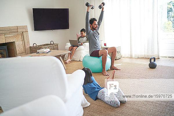 Vater übt mit Hanteln im Wohnzimmer mit Kindern