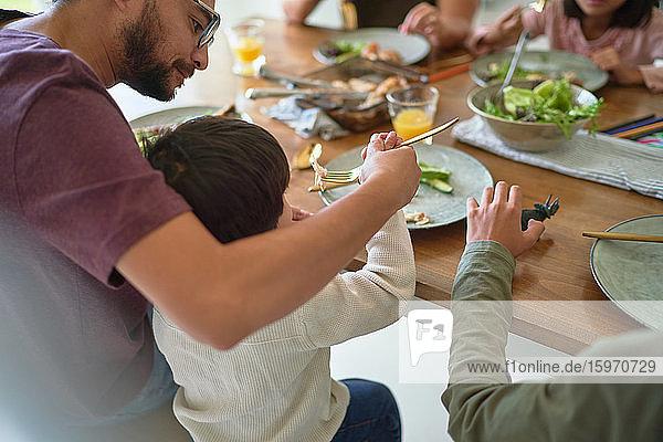 Vater füttert Kleinkind-Sohn am Esstisch