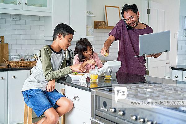 Vater mit Laptop füttert Kinder mit Essen zum Mitnehmen in der Küche