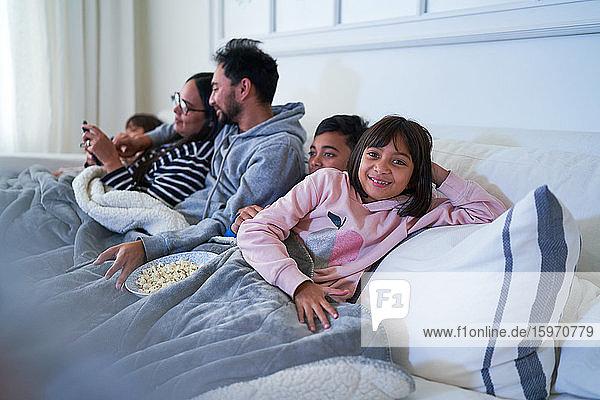 Porträt eines glücklichen Mädchens  das sich mit der Familie auf dem Sofa entspannt