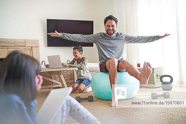 Spielerischer Vater übt mit Kindern auf dem Fitnessball im Wohnzimmer