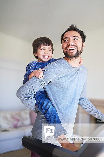 Glücklicher Vater fährt Huckepack mit seinem Sohn auf dem Laufband
