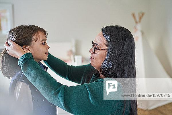 Mutter hilft Tochter bei der Haarpflege
