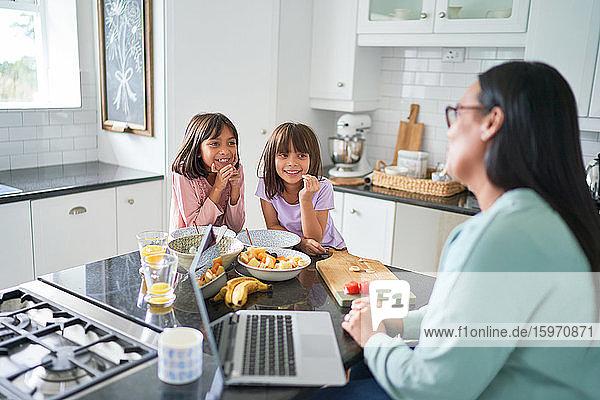 Glückliche Töchter  die frühstücken und der Mutter bei der Arbeit in der Küche zusehen