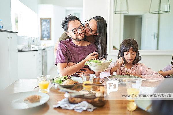Zärtliche Ehefrau küsst Ehemann am Esstisch