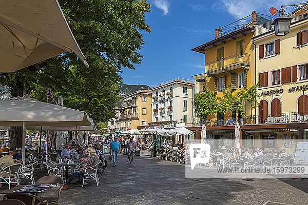 Blick auf Cafés und Besucher auf der Promenade an einem sonnigen Tag  Gardasee  Gardasee  Provinz Verona  Venetien  Italienische Seen  Italien  Europa