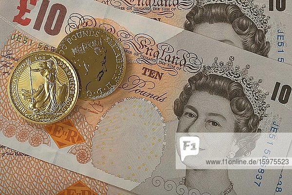 Gold coins  1 ounce  Britannia obverse and reverse Queen Elizabeth II  on 10 pound sterling banknote