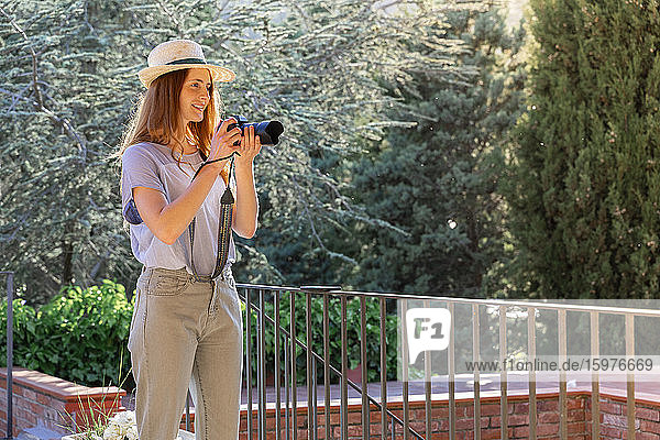 Female photographer wearing straw hat and holding camera on terrace