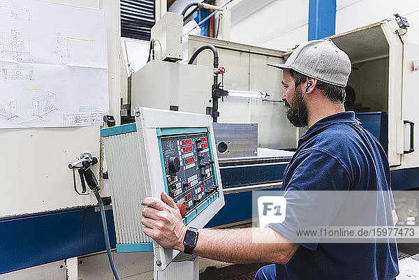 Man operating a machine in a factory