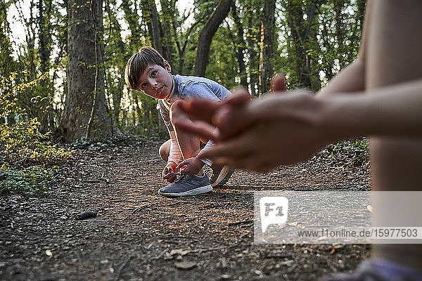 Boy tying his shoelace while looking at sister in forest