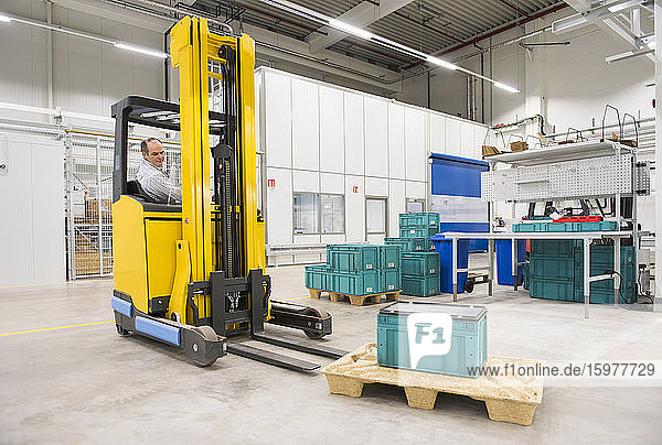 Man on forklift in a factory transporting box