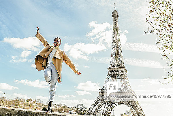 Excited woman jumping from retaining wall with Eiffel Tower in background  Paris  France