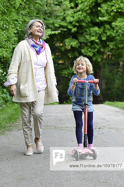 Happy senior woman walking with granddaughter riding push scooter in park