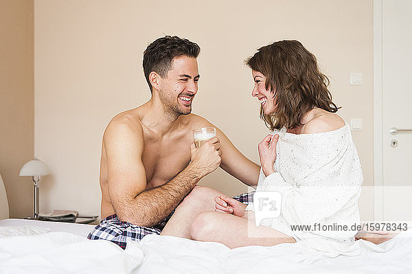 Cheerful young couple looking at each other while sitting on bed at home