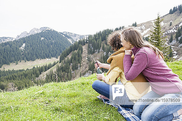 Happy woman leaning on man opening champagne bottle during picnic on mountain