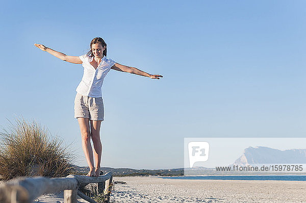 Smiling woman balancing on fence on the beach  Sardinia  Italy