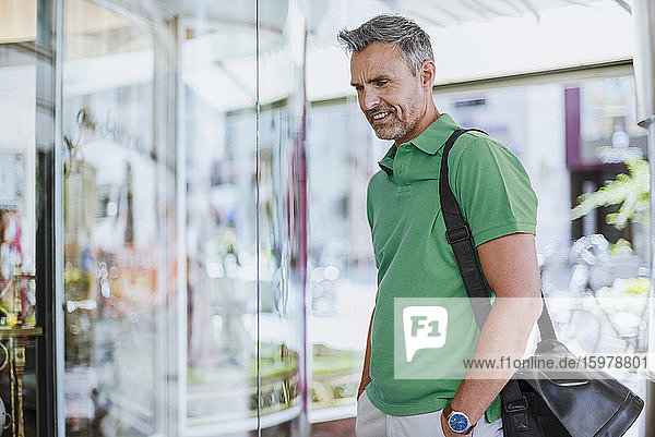 Smiling mature man doing window shopping in mall