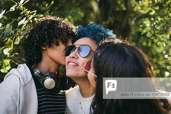 Children kissing mother with blue hair in park