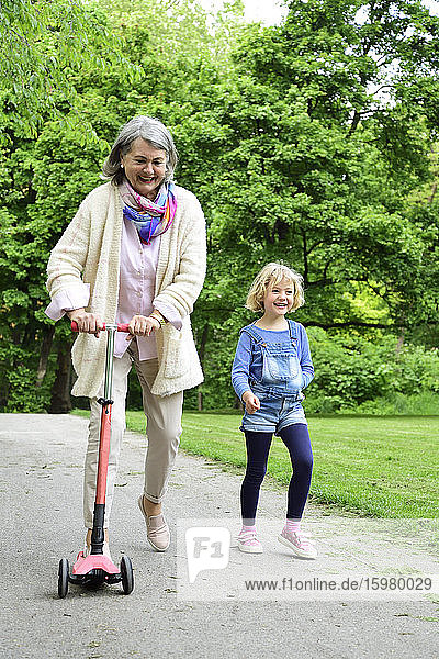 Active senior woman riding push scooter while granddaughter walking in park