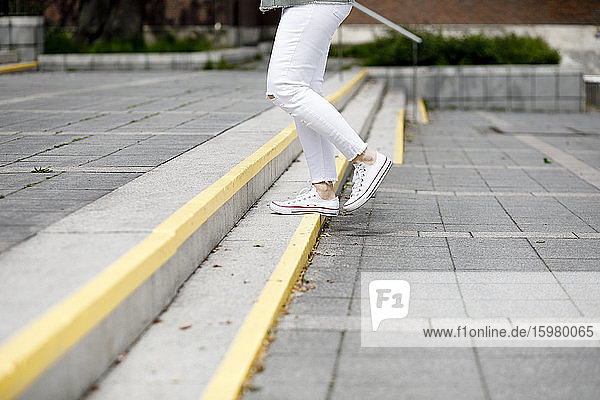 Low section of woman moving up on steps in city