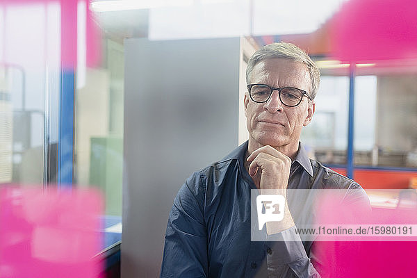 Thoughtful mature male entrepreneur looking at adhesive notes on glass in office