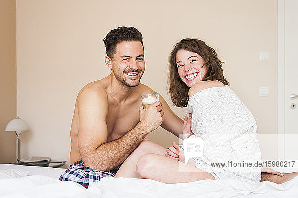 Happy young couple sitting on bed at home