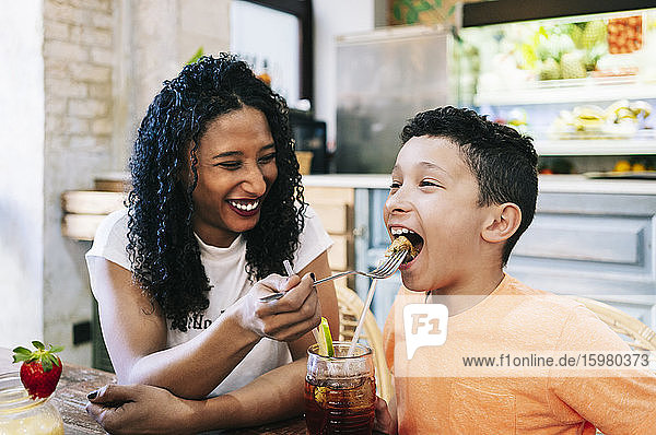 Cheerful young woman feeding son with fork at restaurant