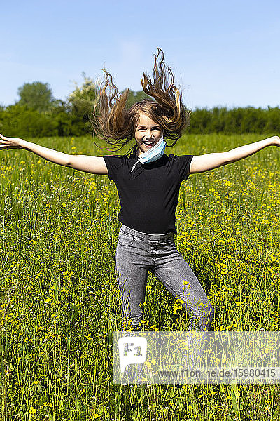 Cheerful girl with arms outstretched wearing mask dancing amidst plants against sky
