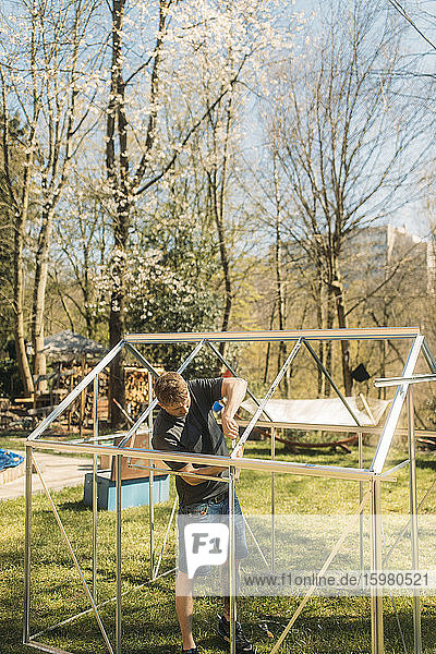 Man building greenhouse in yard during sunny day