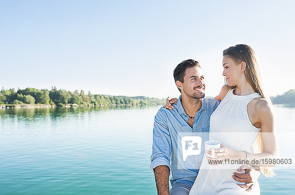 Young couple relaxing in front of a lake