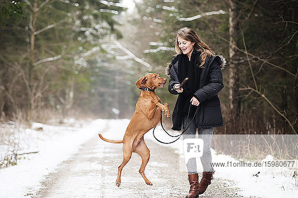 Happy young woman walking while playing with dog on road in forest