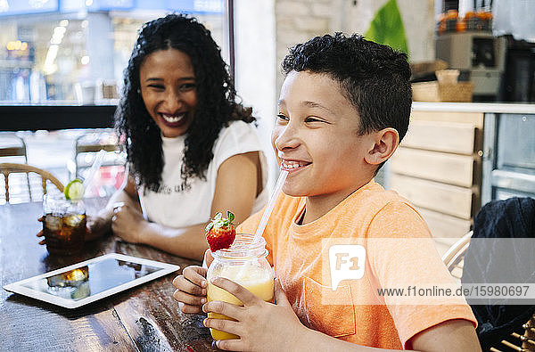 Cheerful woman looking at son sitting with fresh smoothie in restaurant