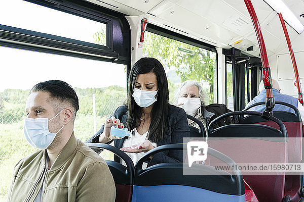 Woman wearing protective mask in public bus disinfecting her hands  Spain