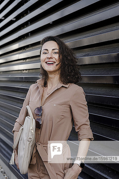Contented businesswoman carrying laptop bag while standing against black shutter