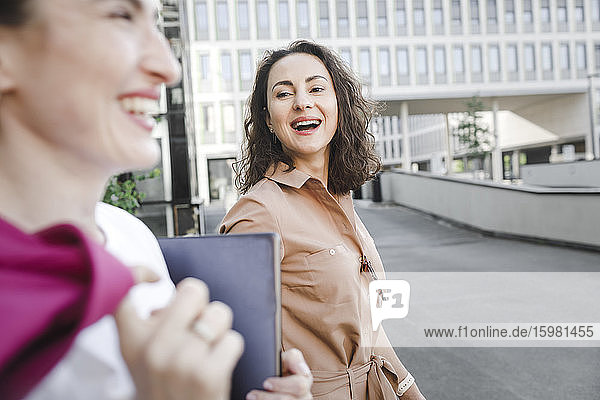 Happy businesswoman talking to colleague while walking against office building