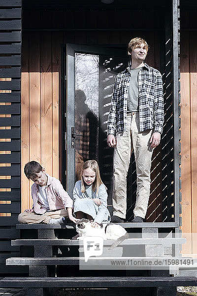 Man standing by children playing with cat on steps outside house during sunny day  Tarusa  Russia