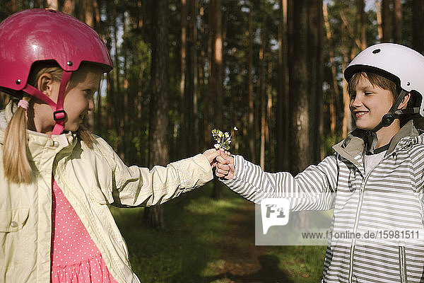 Girl and boy wearing cycling helmets holding flowers in forest