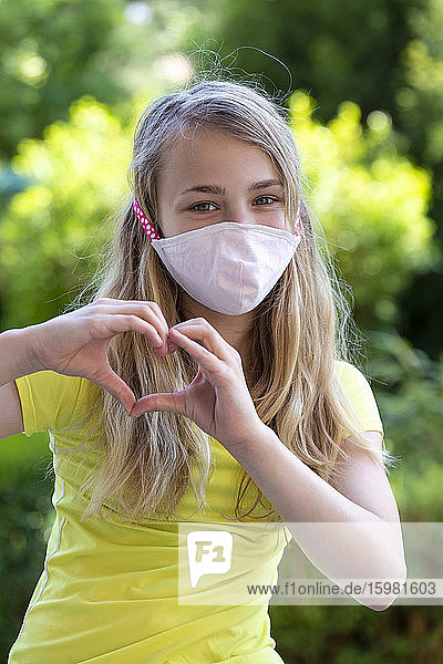 Close-up of girl wearing face mask forming heart shape with hands in park