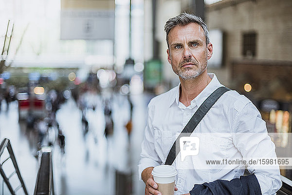 Confident serious businessman holding coffee while standing in city