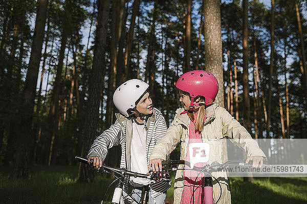 Girl and boy talking while riding bicycles in forest