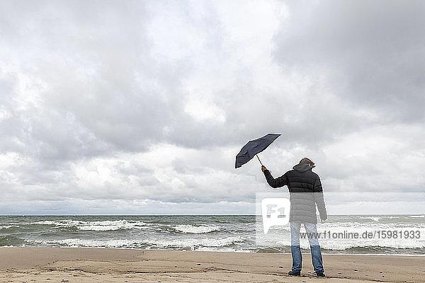 Russia  Kaliningrad Oblast  Zelenogradsk  Man standing on sandy coastal beach with umbrella in hand