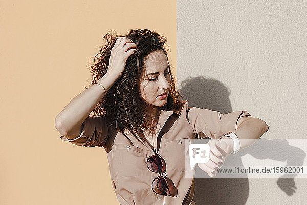 Businesswoman with hand in hair checking smart watch against colorful wall