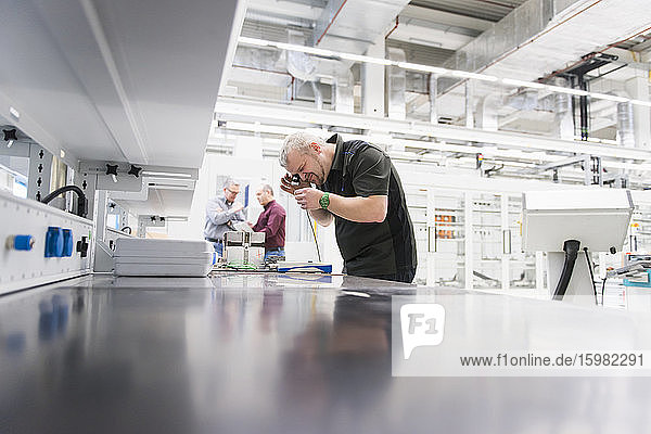 Man examining product in a factory with colleagues in background