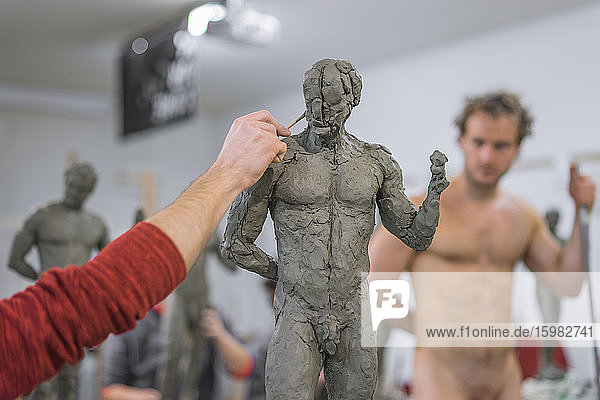 Student forming sculpture  nude model in the background Student forming sculpture, nude model in the background