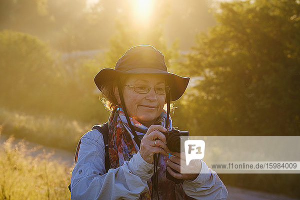 Senior female hiker looking at camera while standing in forest  Bavaria  Germany