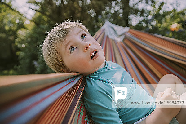 Cute boy looking up while relaxing on hammock at garden during sunny day