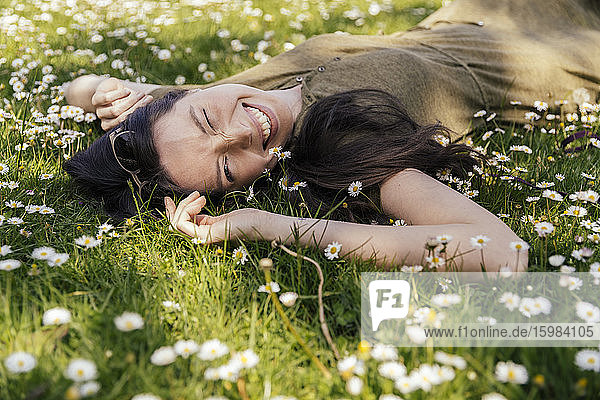 Happy woman enjoying her free time while lying on grass with daisies