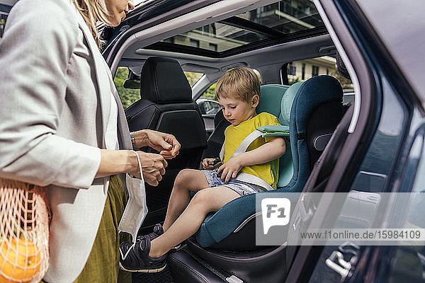 Little boy fastening seat bell of child's seat in car while his mother watching him